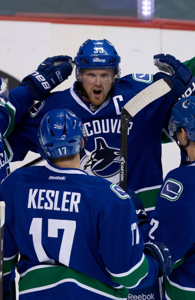 Vancouver Canucks' Daniel Sedin, left, of Sweden, celebrates his goal against the Toronto Maple Leafs with teammates Henrik Sedin, center, Ryan Kesler (17), Dan Hamhuis (2) and Jason Garrison during the first period of an NHL hockey game in Vancouver, British Columbia, on Saturday, Nov. 2, 2013