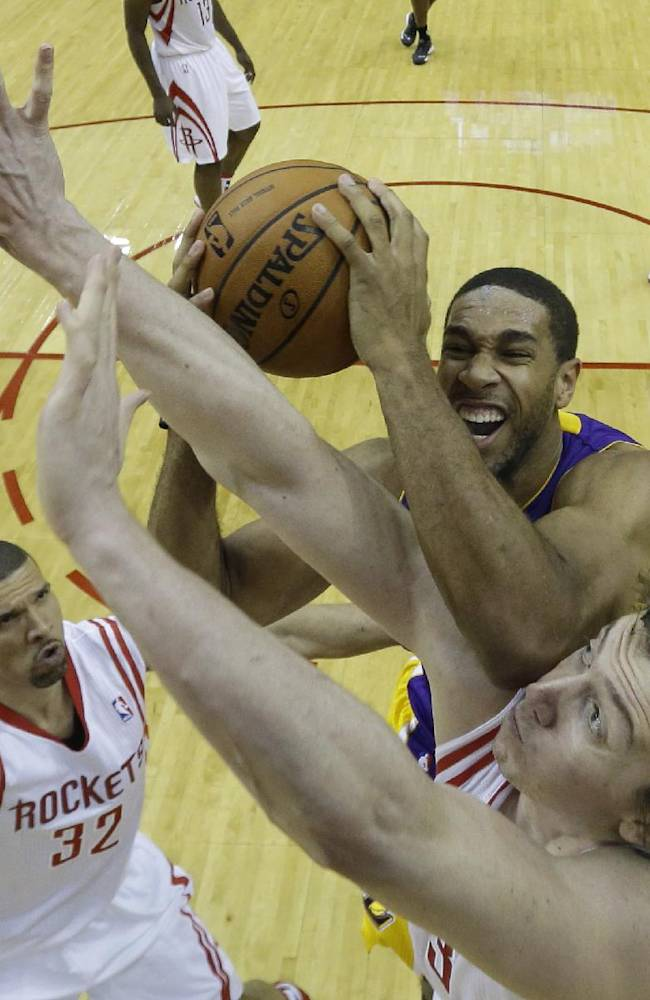 Los Angeles Lakers' Xavier Henry, top, goes up for a shot as Houston Rockets' Omer Asik, bottom, defends during the fourth quarter of an NBA basketball game Thursday, Nov. 7, 2013, in Houston. The lakers won 99-98