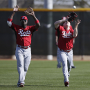 Cincinnati Reds second baseman Brandon Phillips, left, reacts as teammate right fielderJay Bruce makes a catch during a spring training baseball workout Thursday, Feb. 20, 2014, in Goodyear, Ariz The Associated Press
