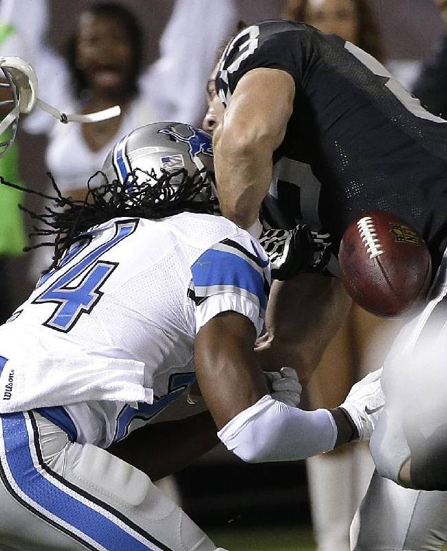 Oakland Raiders tight end Scott Simonson, center, loses his helmet and fumbles as he is hit by Detroit Lions defensive back DeJon Gomes (24) during the fourth quarter of an NFL preseason football game in Oakland, Calif., Friday, Aug. 15, 2014. Detroit recovered the ball