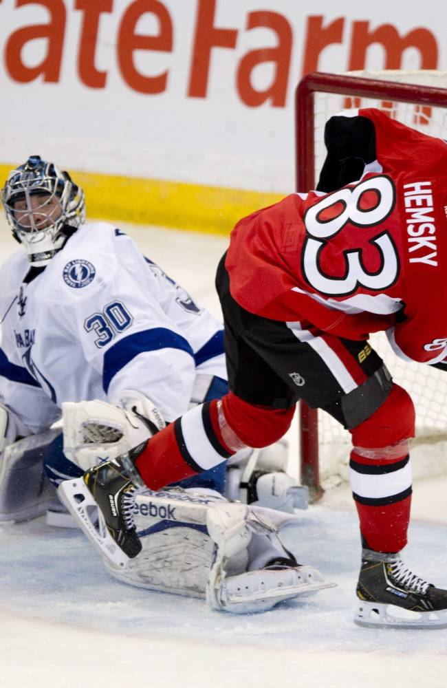 Tampa Bay Lightning defenseman Matt Carle, left, and goalie Ben Bishop watch as Ottawa Senators right wing Ales Hemsky fires the puck into the net during the second period of an NHL hockey game Thursday, March 20, 2014, in Ottawa, Ontario