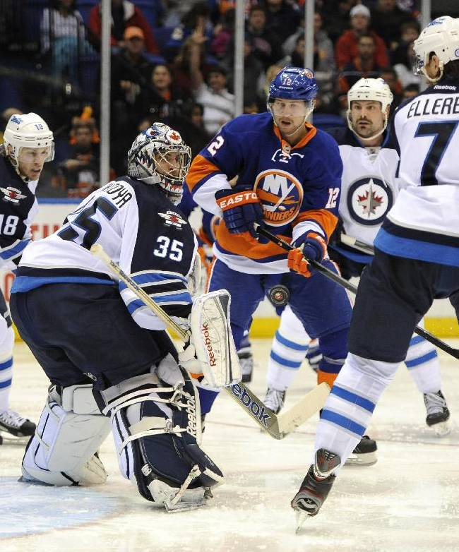 Winnipeg Jets goalie Al Montoya (35) keeps his eyes on an airborne puck as he defends against New York Islanders left wing Josh Bailey (12) in the second period of an NHL hockey game on Wednesday, Nov. 27, 2013, in Uniondale, N.Y. Jets' Bryan Little (18),  Mark Stuart (5) and Keaton Ellerby (7) surround the goal in defense. The Jets won 3-2