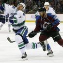 Vancouver Canucks defenseman Dan Hamhuis, left, reacts after getting hit by a high stick wielded by Colorado Avalanche center Marc-Andre Cliche in the first period of an NHL hockey game in Denver on Tuesday, Nov. 4, 2014. Cliche was penalized for the high