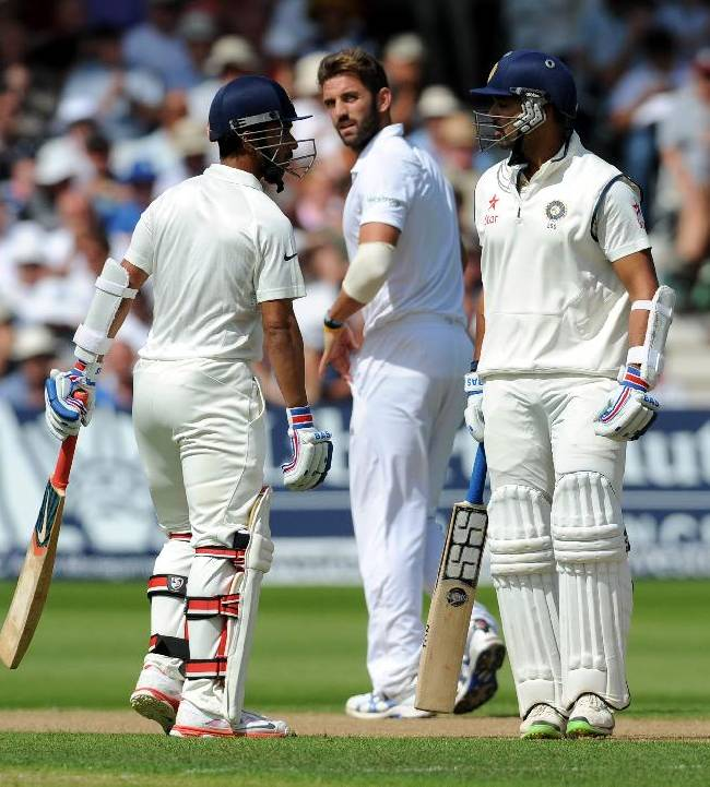 England's bowler Liam Plunkett looks back towards India's Murali Vijay, right, and Ajinkya Rahane, left, during day one of the first Test between England and India at Trent Bridge cricket ground, Nottingham, England, Wednesday, July 9, 2014