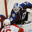 Colorado Avalanche goalie Reto Berra, back, of the Czech Republic, deflects shot as center Matt Duchene, center, pursues the puck with Florida Panthers center Aleksander Barkov, front, of Finland, in the second period of an NHL hockey game in Denver on Tu