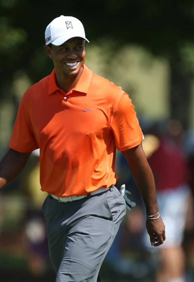 Tiger Woods talks with his caddie as he walks down the first fairway during round one of the 2013 Tour Championship golf tournament at East Lake Golf Club, Thursday, Sept. 19, 2013, in Atlanta. Woods finished in 29th place with a round of 3 over par