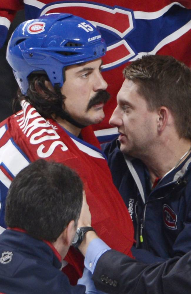 In this Oct. 1, 2013 photo, Montreal Canadiens winger George Parros (15) is treated by medical staff after he hit his head on the ice during a fight with Toronto Maple Leafs winger Colton Orr  during third period NHL action in Montreal. Parros sustained a concussion
