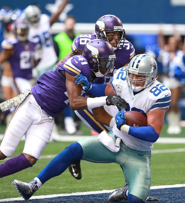 Dallas Cowboys tight end Jason Witten (82) scores a touchdown,tackled by Minnesota Vikings strong safety Mistral Raymond (41) during the second half of an NFL football game Sunday, Nov. 3, 2013, in Arlington, Texas