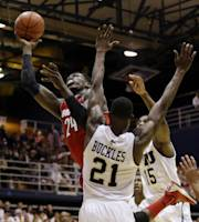 Louisville's Montrezl Harrell (24) goes up to shoot as Florida International's Rakeem Buckles (21) and Tymell Murphy (15) defend in the first half of an NCAA college basketball game, Saturday, Dec. 21, 2013, in Miami. (AP Photo/Lynne Sladky)