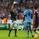 Refree Alberto Undiano Mallenco from Spain shows the yellow card to Manchester City's Vincent Kompany during the Champions League Group E soccer match between FC Bayern Munich and Manchester City at Allianz Arena in Munich, southern Germany, Wednesday Sep