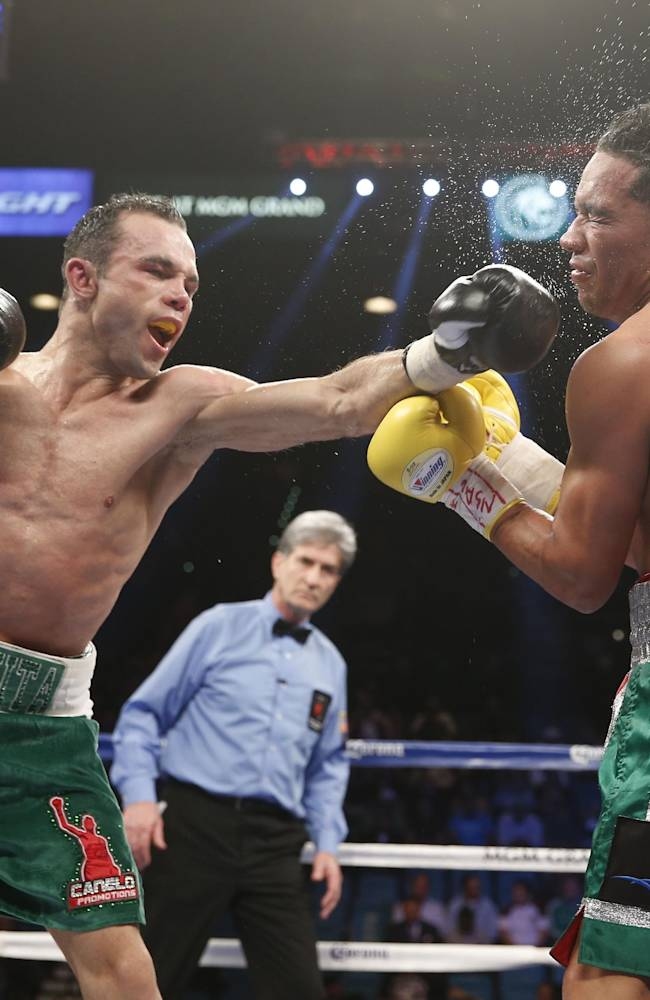 Ricardo Alvarez of Guadalajara Mexico, left, connects with a left to Sergio Thompson of Chetumal Mexico during their WBC lightweight boxing match, Saturday, March 8, 2014, at The MGM Grand Garden Arena in Las Vegas. Thompson won by unanimous decision