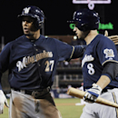 Milwaukee Brewers' Carlos Gomez (27) celebrates with Ryan Braun after Gomez scored on a sacrifice fly by Braun in the seventh inning of a baseball game against the Philadelphia Phillies on Thursday, April 10, 2014, in Philadelphia. The Brewers won 6-2 The