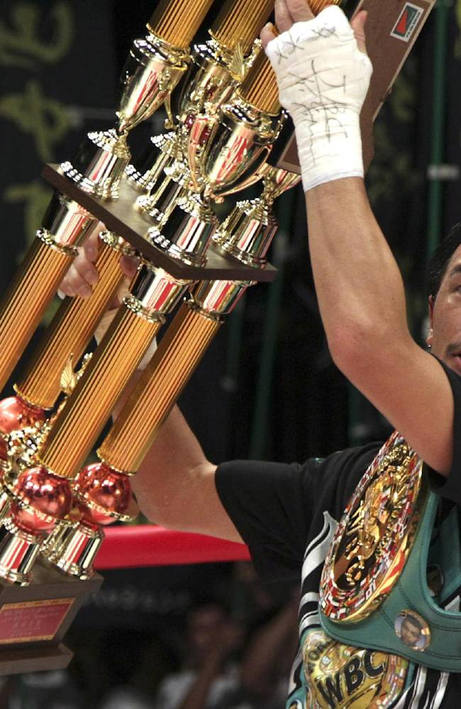 Japanese champion Shinsuke Yamanaka holds up the winner's trophy after knocking down Mexican challenger Alberto Guevara in the ninth round to defend his WBC bantamweight title in Tokyo, Sunday, Nov. 10, 2013