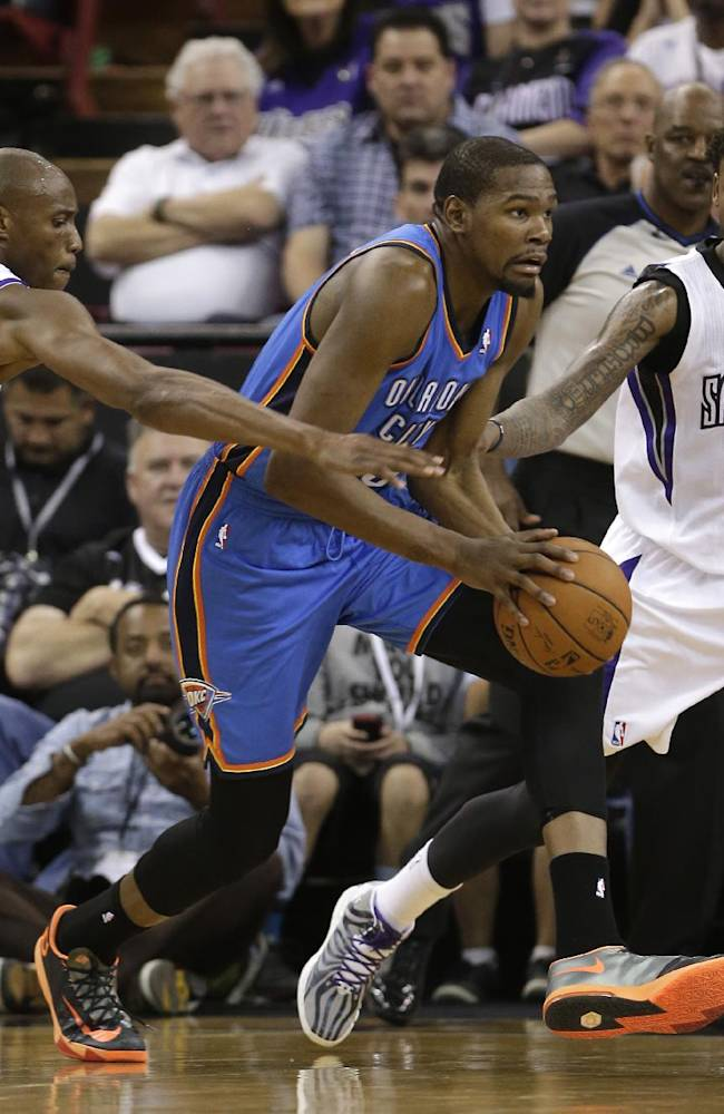 Oklahoma City Thunder forward Kevin Durant, center, dribbles between Sacramento Kings Travis Outlaw, left, and Ben McLemore during the third quarter of an NBA basketball game, Tuesday, April 8, 2014, in Sacramento, Calif.  The Thunder won 107-92