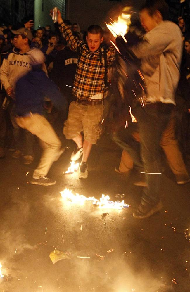 Kentucky fans gather at the intersection of Elizabeth and State Streets near campus in Lexington, Ky.,  and burn shirts after losing the NCAA College basketball Championship game to UConn Monday, April 7, 2014