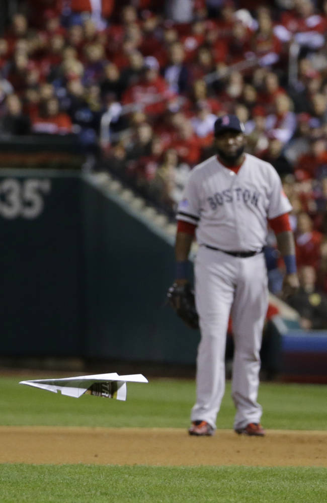 Boston Red Sox David Ortiz watches as a paper plane lands on the field during the seventh inning of Game 5 of baseball's World Series against the St. Louis Cardinals Monday, Oct. 28, 2013, in St. Louis