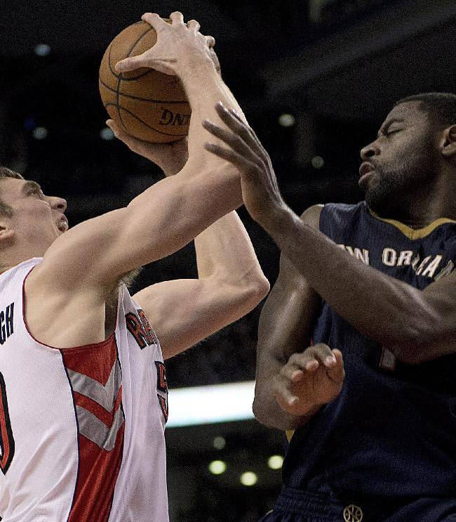 Toronto Raptors forward Tyler Hansbrough, left, drives into New Orleans Pelicans guard Tyreke Evans during fourth quarter NBA action in Toronto, Monday, Feb. 10, 2014