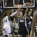 San Antonio Spurs guard Manu Ginobili, right, of Argentina, does a reverse layup against Sacramento Kings forward Jason Thompson, during the third quarter of an NBA basketball game in Sacramento, Calif., Friday, March 21, 2014. The Spurs won 99-79 The