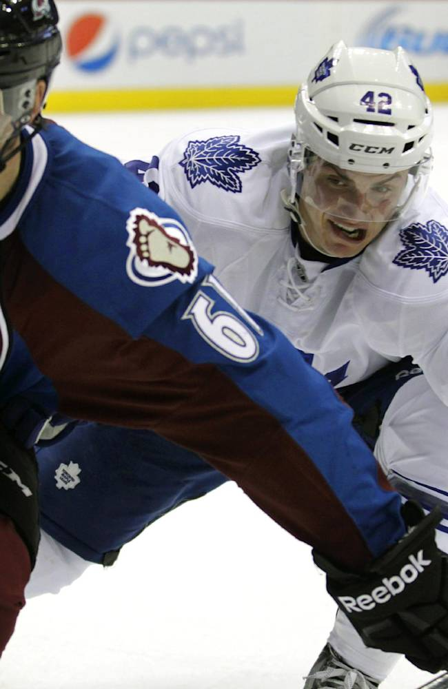 Colorado Avalanche defenseman Andre Benoit (61) and Toronto Maple Leafs center Tyler Bozak (42) skate to the puck during the second period of an NHL game in Denver on Tuesday, Jan. 21, 2014