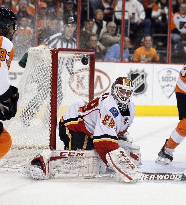 Philadelphia Flyers' Jakub Voracek, left, and Calgary Flames goalie Reto Berra, center, eye the puck Berra deflected that was a pass intended for Claude Giroux, right, during the second period of an NHL hockey game, Saturday, Feb. 8, 2014, in Philadelphia. The Flyers won 2-1