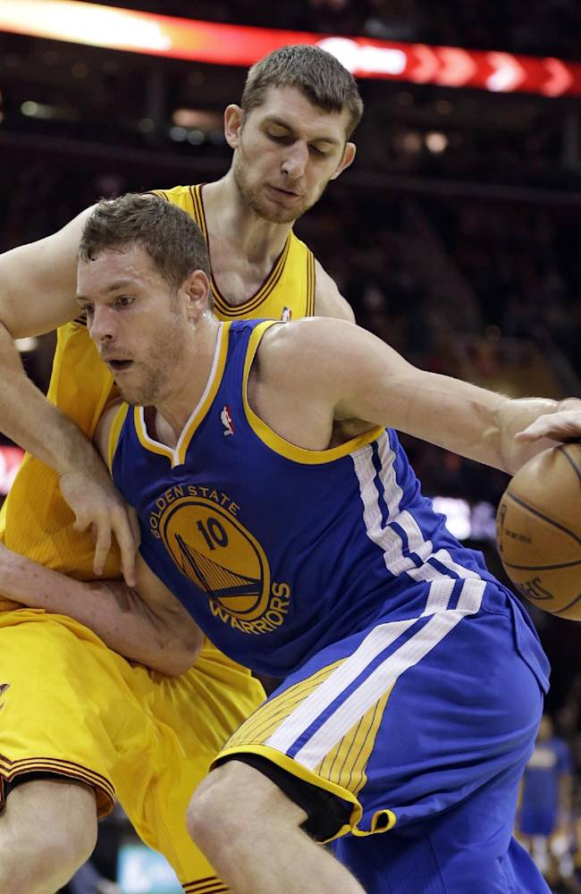 Golden State Warriors' David Lee (10) drives around Cleveland Cavaliers' Tyler Zeller (40) during an NBA basketball game, Sunday, Dec. 29, 2013, in Cleveland. The Warriors defeated the Cavaliers 108-104 in overtime