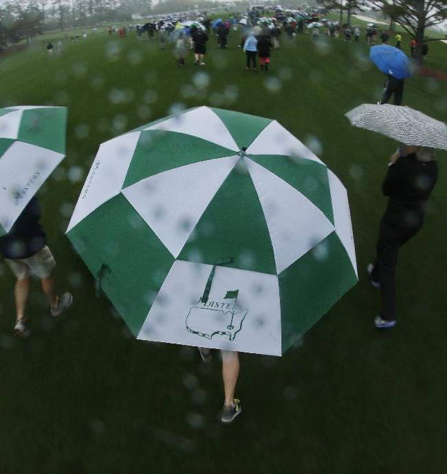 Spectators walk off the course after play was suspended because of severe weather during the first day of practice for the Masters golf tournament Monday, April 7, 2014, in Augusta, Ga
