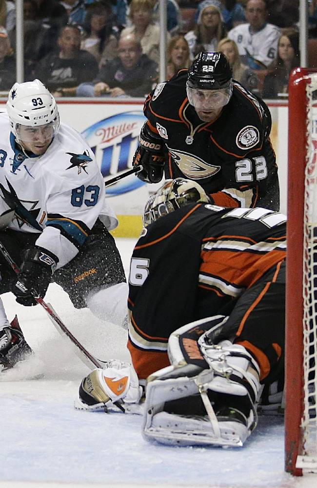 Anaheim Ducks goalie John Gibson, right, stops a shot by San Jose Sharks' Matt Nieto, left, as Ducks' Francois Beauchemin watches during the first period of an NHL hockey game on Wednesday, April 9, 2014, in Anaheim, Calif
