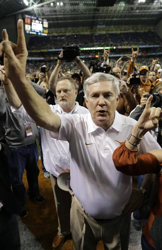 Texas coach Mack Brown holds up the