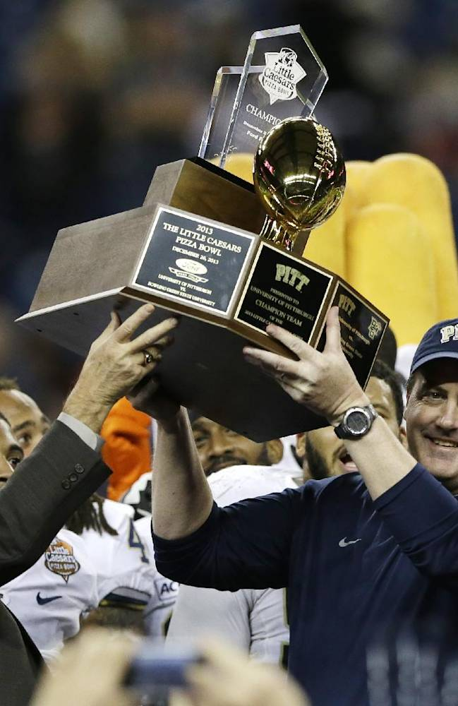 Pittsburgh coach Paul Chryst is presented with the championship trophy by Lloyd Carr, left, after the Panthers defeated Bowling Green 30-27 in the Little Caesars Pizza Bowl NCAA college football game, Thursday, Dec. 26, 2013. in Detroit