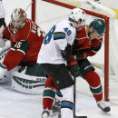 Minnesota Wild defenseman Christian Folin, right, of Sweden, battles San Jose Sharks center Tomas Hertl (48), of the Czech Repbulic, for the puck as Wild goalie Darcy Kuemper, left, watches during the first period of an NHL hockey game in St. Paul, Minn.,