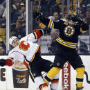Calgary Flames left wing Lance Bouma, left, crashes into Boston Bruins defenseman Matt Bartkowski along the boards during the first period of an NHL hockey game in Boston, Tuesday, Dec. 17, 2013. (AP Photo/Elise Amendola)