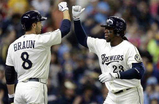 Milwaukee Brewers' Rickie Weeks (23) high-fives Ryan Braun after Weeks' two-run home run against the Chicago White Sox during the first inning of an exhibition baseball game, Saturday, March 30, 2013, in Milwaukee