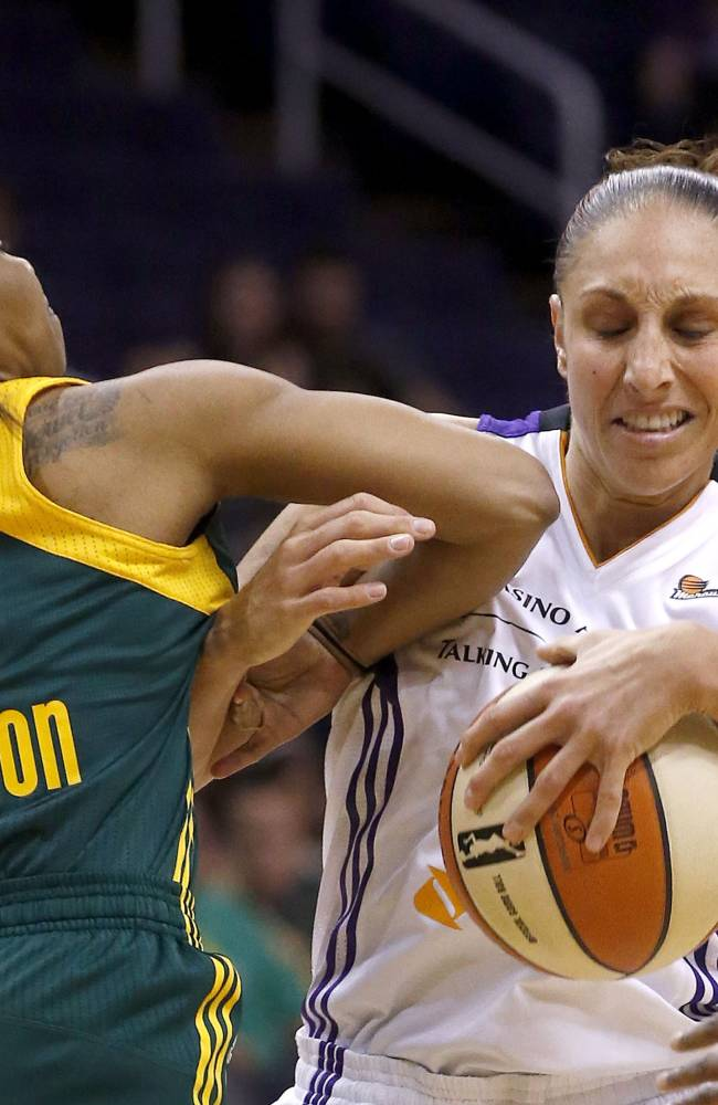 Phoenix Mercury's Diana Taurasi, right, gets fouled by Seattle Storm's Temeka Johnson (2) during the second half of a WNBA basketball game on Tuesday, June 3, 2014, in Phoenix