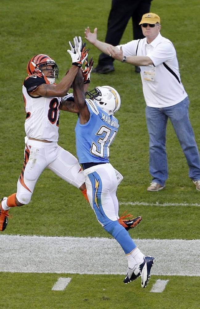 Cincinnati Bengals wide receiver Marvin Jones, left, can't make the catch as San Diego Chargers cornerback Richard Marshall defends and a sidelines onlooker gets ready to catch during the second half of an NFL football game Sunday, Dec. 1, 2013, in San Diego