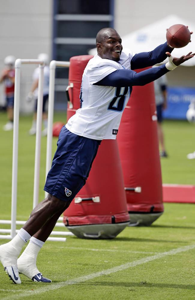 In this July 27, 2014, photo, Tennessee Titans wide receiver Derek Hagan reaches for a pass during NFL football training camp in Nashville, Tenn. Hagan sat around all last season hoping for a phone call from an NFL team. None came. This offseason, the receiver only got one call, and it came in mid-June. Now he's in training camp with the Tennessee Titans hoping to earn a roster spot keeping him around the league for another season