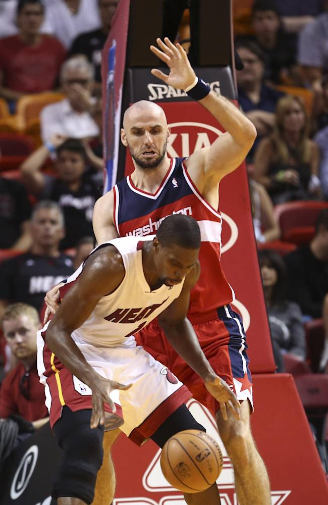 Washington Wizards' Marcin Gortat (4) blocks a shot by Miami Heat's Chris Bosh (1) during the second half of an NBA basketball game in Miami, Sunday, Nov. 3, 2013