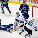Vancouver Canucks' Daniel Sedin, left, of Sweden, and Dan Hamhuis, top, celebrate a goal by teammate Kevin Bieksa as San Jose Sharks' goalie Antti Niemi, centre, of Finland, and Justin Braun, right, look on during second period NHL hockey action in Vancou