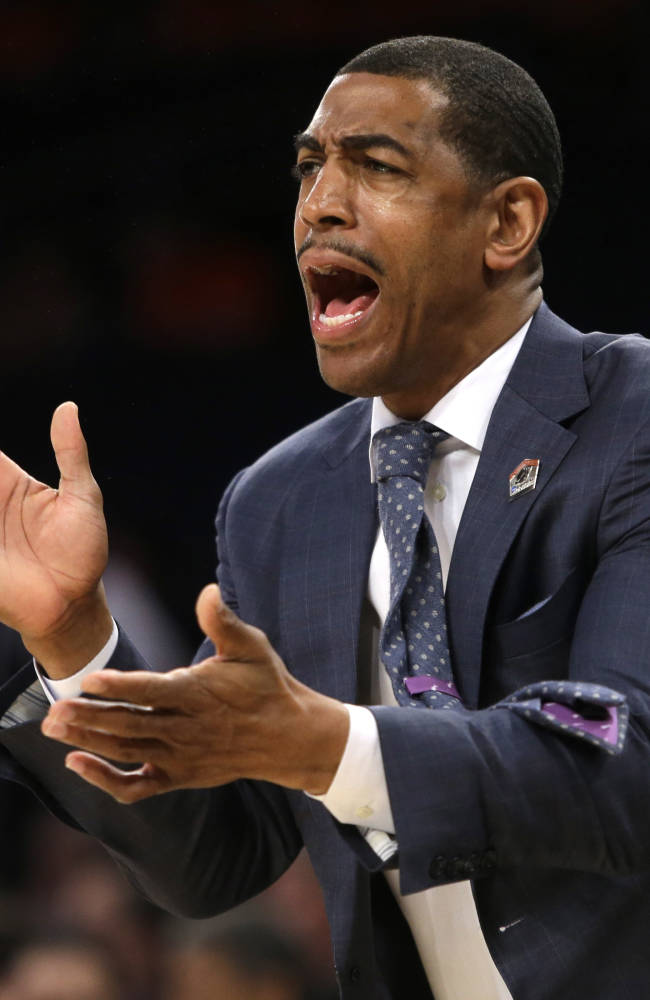 In this March 28, 2014 file photo, Connecticut coach Kevin Ollie shouts instructions during the first half in a regional semifinal against Iowa State in the NCAA men's college basketball tournament in New York. Ollie is listening to job offers, but isn't looking to leave Connecticut. The 41-year-old coach, who spent 13 years as an NBA journeyman before returning to his alma mater, has been linked to several NBA job openings