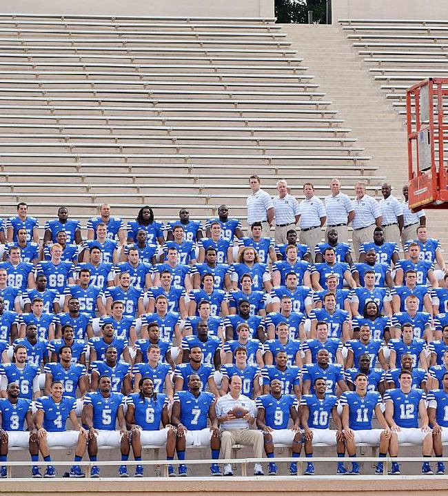Duke football coach David Cutcliffe is sitting in front with his players and coaches for a team photo with Duke photographer's Jon Gardiner (R) during media day, at Duke Wallace Wade Stadium, Durham, N.C., Sunday, Aug. 17, 2014