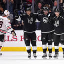 Los Angeles Kings right wing Marian Gaborik, second from left, of Slovakia, celebrates a goal by defenseman Jake Muzzin with teammates center Anze Kopitar, second from right, of Slovenia, and defenseman Drew Doughty, right, as Chicago Blackhawks center Jonathan Toews skates away during the third period of an NHL hockey game, Wednesday, Jan. 28, 2015, in Los Angeles. The Kings won 4-3. (AP Photo/Mark J. Terrill)