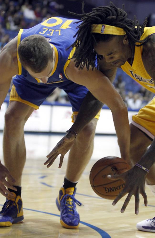 Golden State Warriors center David Lee, left, works against Los Angeles Lakers center Jordan Hill, right for the ball in the first quarter during an NBA basketball preseason game Saturday, Oct. 5, 2013, in Ontario, Calif