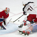 Columbus Blue Jackets' Nick Foligno, center, slides in on Montreal Canadiens' goaltender Carey Price, left, as Canadiens' Mike Weaver defends during the second period of an NHL hockey game in Montreal, Thursday, March 20, 2014 The Associated Press