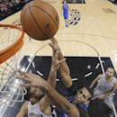 Dallas Mavericks' Brandan Wright shoots as San Antonio Spurs' Tim Duncan (21) defends during the first half of an NBA basketball game, Sunday, March 2, 2014, in San Antonio The Associated Press