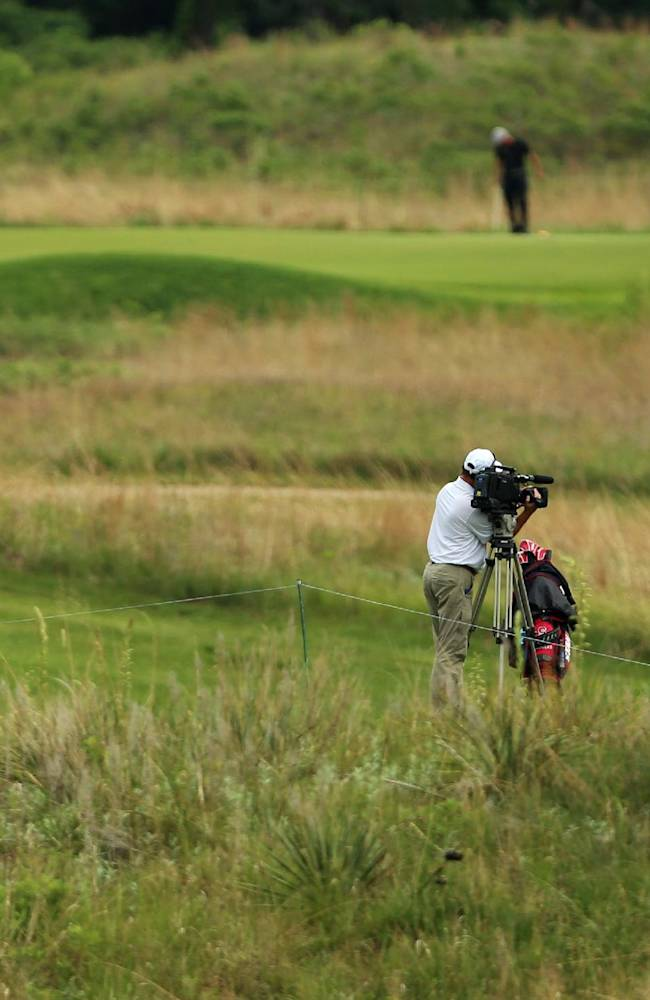 A group of people and a television camera follow Stanford's Patrick Rodgers, right, on the eighth hole during the first round of the NCAA college men's golf championship on Saturday, May 24, 2014, at Prairie Dunes Country Club in Hutchinson, Kan