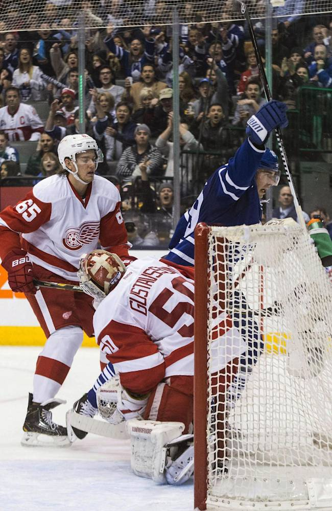 Toronto Maple Leafs' Joffrey Lupul, right, celebrates scoring against Detroit Red Wings goaltender Jonas Gustavsson, center, as Detroit's Danny Dekeyser looks on during second period NHL hockey action in Toronto on Saturday, Dec 21, 2013