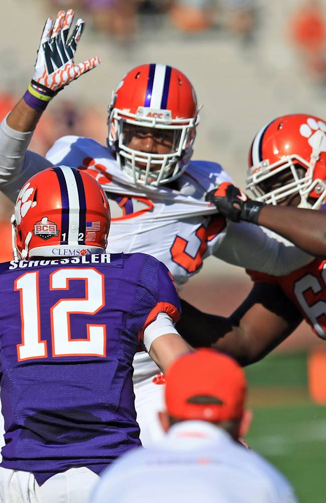 Clemson defensive end Vic Beasley, center, is held by offensive guard David Beasley, right, as he pressures quarterback Nick Schuessler (12) during an NCAA college football spring game at Memorial Stadium in Clemson, S.C., Saturday, April 12, 2014