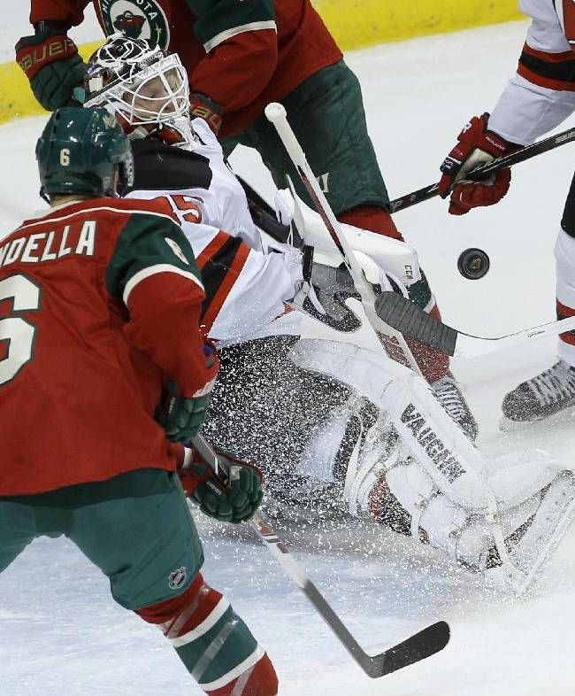 New Jersey Devils goalie Cory Schneider (35) deflects a shot as Minnesota Wild defenseman Marco Scandella (6) watches during the first period of an NHL hockey game in St. Paul, Minn., Sunday, Nov. 3, 2013