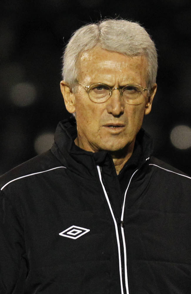 Canada's head coach Benito Floro arrives at the dugout before the start of their international soccer match against Australia at Craven Cottage, London, Tuesday, Oct. 15, 2013