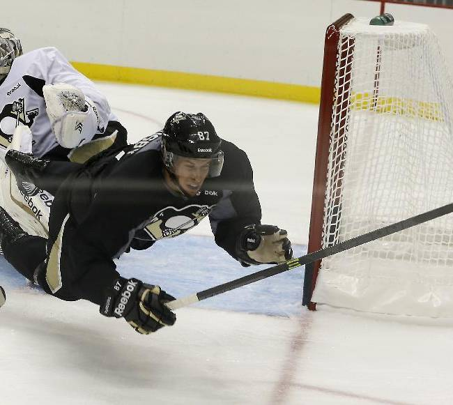 Pittsburgh Penguins' Sidney Crosby, right, is seen through the glass as he tumbles over goalie Marc-Andre Fleury during a scrimmage on the first day on the ice at NHL hockey camp on Thursday, Sept. 12, 2013 in Pittsburgh