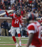 Mississippi quarterback Bo Wallace (14) throws a pass to an open receiver during the first half of an NCAA college football game against Arkansas at Vaught-Hemingway Stadium in Oxford, Miss., on Saturday, Nov. 9, 2013. (AP Photo/Rogelio V. Solis)